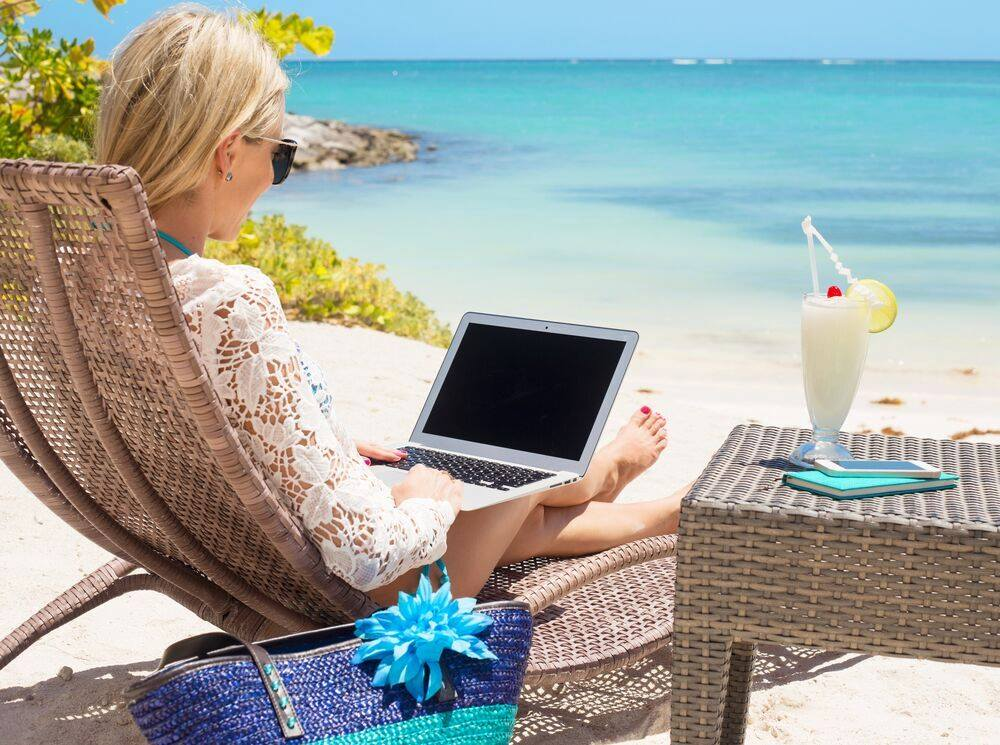Woman with computer on beach